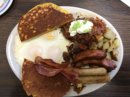 The Cowboy's Breakfast ($12) -- Three eggs, smoked bacon, sausage, grilled chorizo and chili smothered hashbrowns. Served with corn cakes. Chuckwagon not included.